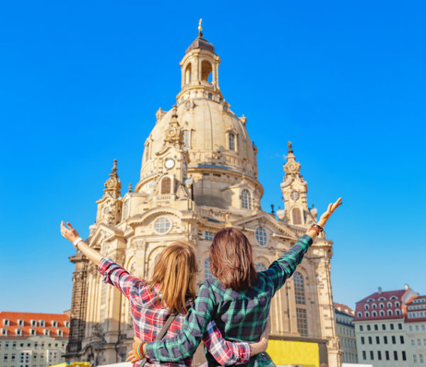 Wo happy women hugging and looking at the main attraction of Dresden Frauenkirche